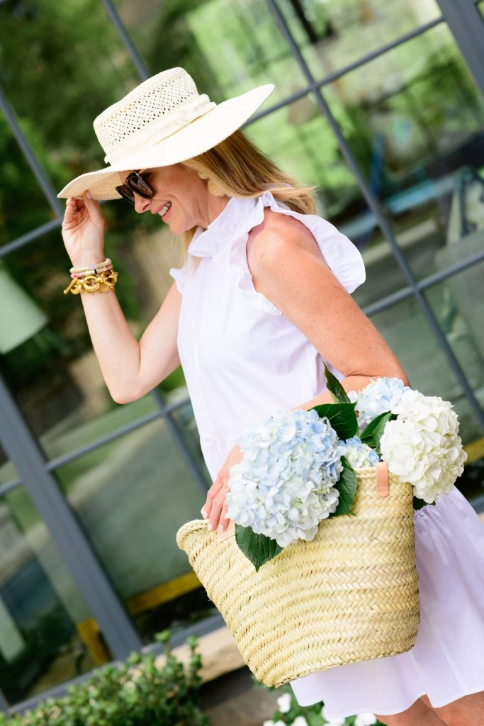 Tanya Foster in white dress and sun hate and mango straw bag with flowers