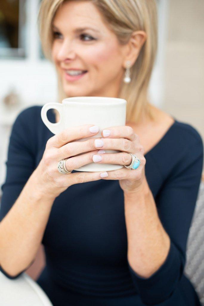 Tanya foster in a black dress holding a coffee mug